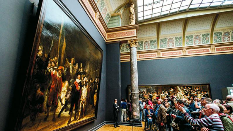 """Los visitantes observan """"The Night Watch"""" de Rembrandt en el Rijksmuseum de Amsterdam el 17 de mayo de 2015. (ROBIN VAN LONKHUIJSEN/AFP/GETTY IMAGES)"""