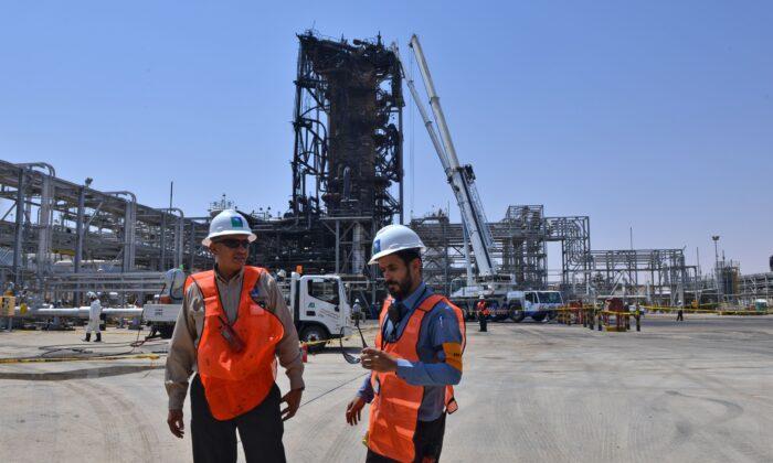 Técnicos de la compañía petrolera Aramco se encuentran cerca de una instalación muy dañada en la planta de procesamiento de petróleo de Khurais en Arabia Saudita, el 20 de septiembre de 2019 (FAYEZ NURELDINE/AFP vía Getty Images)