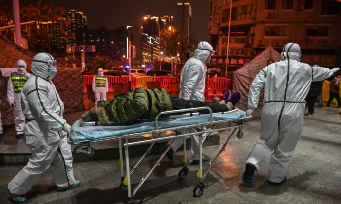 Miembros del personal médico que llevan ropa protectora para ayudar a detener la propagación de un virus mortal que comenzó en la ciudad, llegan con un paciente al Hospital de la Cruz Roja de Wuhan, China, el 25 de enero de 2020. (Hector Retamal/AFP a través de Getty Images)
