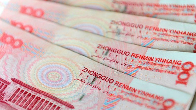 Una ilustración de billetes de 100 yuanes en moneda china emitidos por el Banco Popular de China, con una imagen del parlamento construyendo el Gran Salón del Pueblo en la parte posterior el 12 de noviembre de 2010 en Beijing. (FREDERIC J. BROWN/AFP via Getty Images)