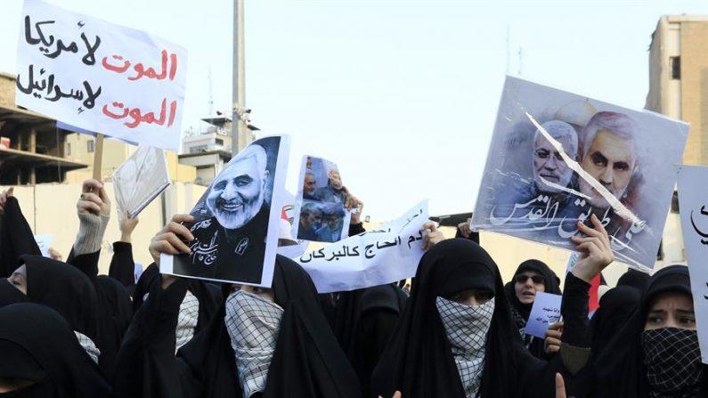 Os partidários das forças de mobilização popular dos grupos armados xiitas iraquianos apoiados pelo Irã exibem as fotos do general Qasem Soleimani e uma placa em árabe 'Morte à América, morte a Israel' durante uma procissão fúnebre na cidade de Karbala, sul de Bagdá, Iraque, em 04 de janeiro de 2020 (EFE / EPA / FURQAN AL-AARAJI)