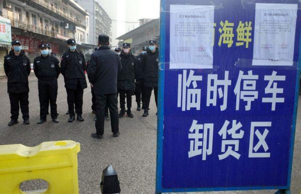 Seguranças guardam a frente do mercado de frutos do mar em Huanan, onde as autoridades de saúde dizem que um homem que morreu de doença respiratória comprou produtos, na cidade de Wuhan, província de Hubei, em 12 de janeiro de 2020 (NOEL CELIS / AFP via Getty Images)