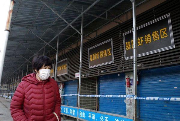 Mulher passa perto do mercado atacadista de frutos do mar em Huanan, fechado, onde as autoridades de saúde dizem que um homem que morreu de doença respiratória comprou produtos na cidade de Wuhan, província de Hubei, em 12 de janeiro de 2020 ( NOEL CELIS / AFP via Getty Images)