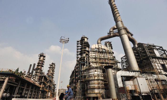 Un trabajador montando una bicicleta en una refinería de petróleo de Sinopec de China, en Wuhan, provincia de Hubei, centro de China, el 10 de mayo de 2011. (STR / AFP / Getty Images)