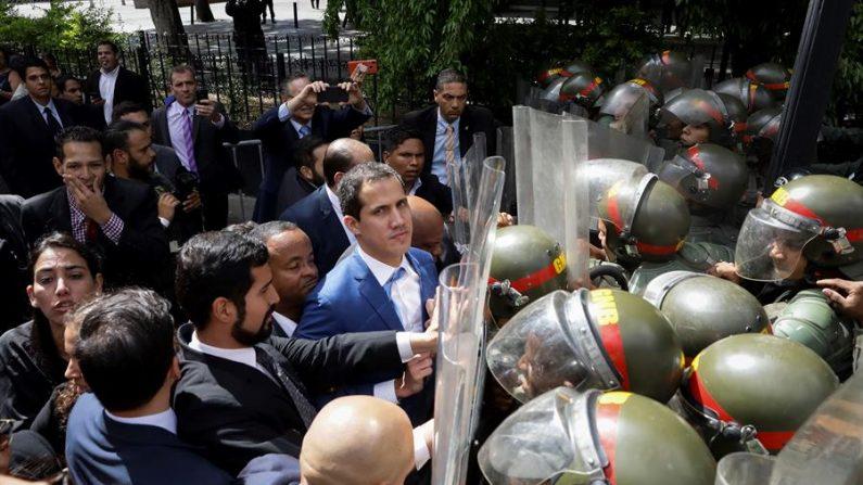 El líder opositor venezolano Juan Guaidó acompañado de un grupo de opositores forcejea con la policía al ver impedida su entrada a la sede de la Asamblea Nacional el 5 de enero de 2020, en Caracas (Venezuela). (EFE/ Rayner Peña)