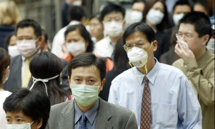La gente usa máscaras en la calle para protegerse contra un virus mortal de neumonía en Hong Kong, el 31 de marzo de 2003. (Peter Parks/AFP/GettyImages)