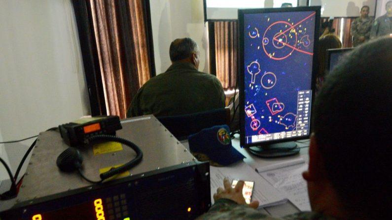 Membros de uma equipe trinacional da Força Aérea do Brasil, Colômbia e Peru observam, em um centro de controle, exercícios conjuntos destinados a aprimorar táticas e estratégias para combater o narcotráfico em suas fronteiras aéreas em Iquitos, Peru, em 20 de junho de 2017 (CRIS BOURONCLE / AFP via Getty Images)