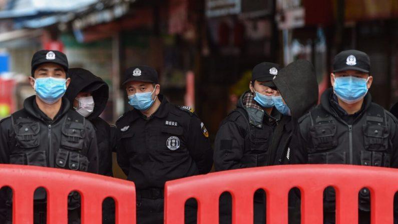 Un grupo de policías y guardias de seguridad se encuentra en las afueras del Mercado Mayorista de Mariscos de Huanan donde el coronavirus fue detectado el 24 de enero de 2020. (Hector Retamal/AFP vía Getty Images)