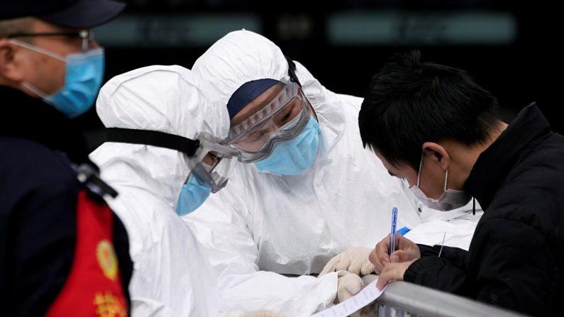 Personal con máscaras protectoras revisan a un pasajero en la estación de tren de Shanghai, China, mientras el país es afectado por un brote de un nuevo coronavirus el 2 de febrero de 2020. (Aly Song/Reuters)