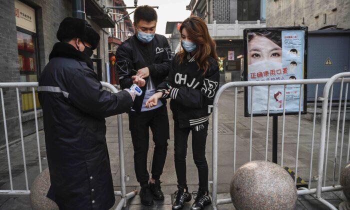 Un guardia de seguridad chino toma la temperatura de una pareja al entrar en una calle comercial casi vacía en Beijing, China, el 12 de febrero de 2020. (Kevin Frayer/Getty Images)