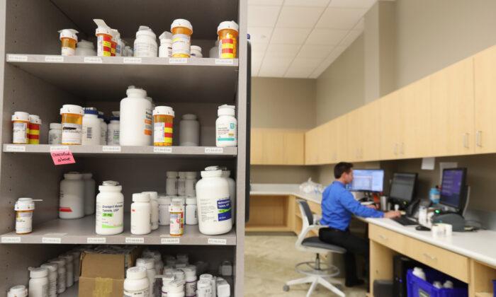 Un técnico farmacéutico trabaja en una computadora mientras los frascos de medicamentos están en los estantes de la farmacia central de Intermountain Heathcare en Midvale, Utah, el 10 de septiembre de 2018. (George Frey/Getty Images)