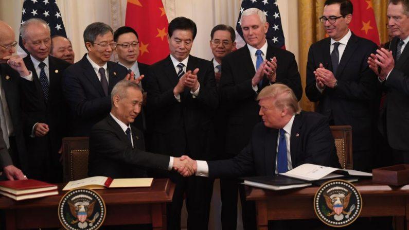 El presidente de EE.UU., Donald Trump (d), y el viceprimer ministro de China, Liu He (i), el principal negociador comercial del país, se dan la mano al firmar acuerdos comerciales entre los EE.UU. y China durante una ceremonia en la Sala Este de la Casa Blanca en Washington, DC el 15 de enero de 2020. (SAUL LOEB/AFP/Getty Images)