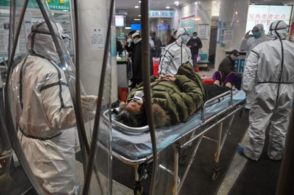 Miembros del personal médico con ropa de protección llegan con un paciente al Hospital de la Cruz Roja de Wuhan, China, el 25 de enero de 2020. (Hector Retamal/AFP a través de Getty Images)