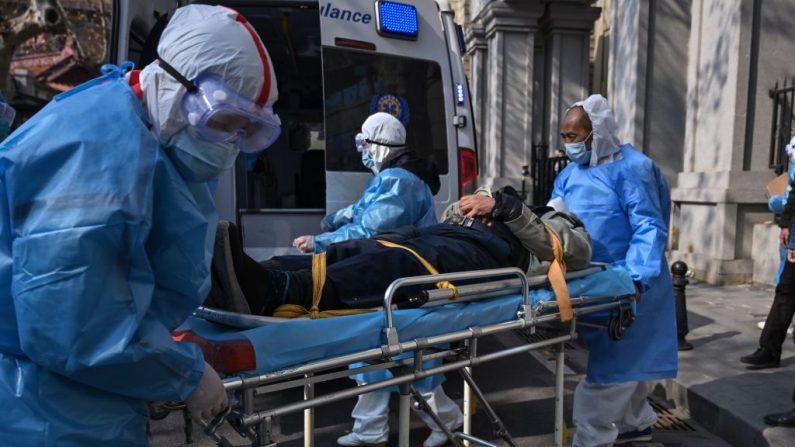 Se ve a personal médico con trajes de protección llevando a un paciente de un apartamento que se sospecha que tiene el nuevo coronavirus, en la provincia de Hubei, el 30 de enero de 2020. (Hector RETAMAL/AFP a través de Getty Images)