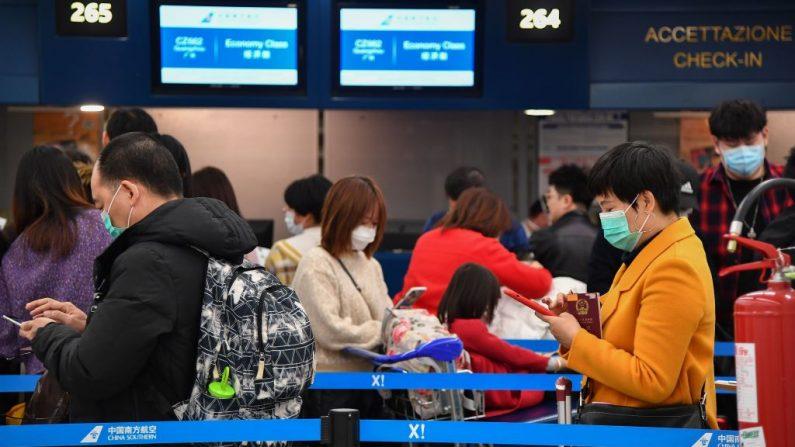 Un pasajero chino (d) que lleva una máscara repiratoria y otros esperan en fila para facturar en el mostrador de China Southern el 31 de enero de 2020 en una terminal del aeropuerto de Fiumicino en Roma, Italia. (TIZIANA FABI/AFP/Getty Images)