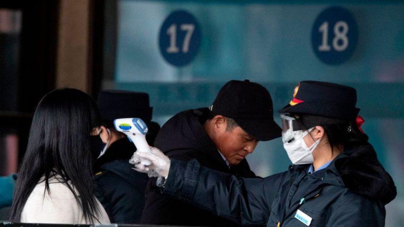 Esta foto tomada el 1 de febrero de 2020 muestra al personal de seguridad comprobando la temperatura de un pasajero con una máscara facial en la estación de ferrocarril de Beijing. - El número de infecciones en el brote de coronavirus de China ha pasado de 14.300 en todo el país con 2.590 nuevos casos confirmados, dijo la Comisión Nacional de Salud el 2 de febrero. (Foto de NOEL CELIS / AFP) (Foto de NOEL CELIS/AFP vía Getty Images)