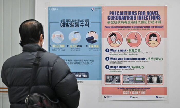 Un hombre con una máscara facial habla por teléfono móvil delante de un cartel con precauciones contra el nuevo coronavirus que se originó en el centro de China, en una estación de metro de Seúl el 10 de febrero de 2020. (Jung Yeon-je/AFP vía Getty Images)