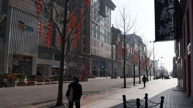 Una mujer lleva una mascarilla facial protectora mientras camina por la calle comercial Wangfujing ahora desierta y que antes era una calle bulliciosa en el centro de Beijing el 10 de febrero de 2020. (Foto de GREG BAKER/AFP vía Getty Images)