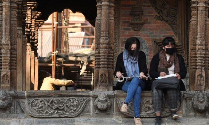 Residentes con mascarillas protectoras sentados en la plaza Patan Durbar en Katmandú, Nepal, el 10 de febrero de 2020. (Prakash Mathema/AFP vía Getty Images)