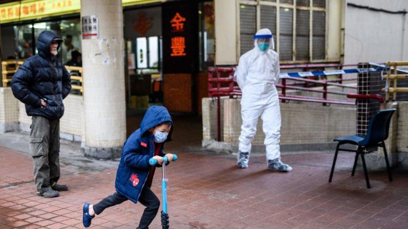 Un niño con una máscara facial pasa en su scooter por delante de un oficial de policía (de) que lleva equipo de protección fuera de Hong Mei House en Cheung Hong Estate en Hong Kong el 11 de febrero de 2020, después de la evacuación de más de 100 personas de un bloque de viviendas ocurrido cuando cuatro residentes de dos apartamentos diferentes dieran positivo en el nuevo coronavirus. (ANTHONY WALLACE / AFP vía Getty Images)
