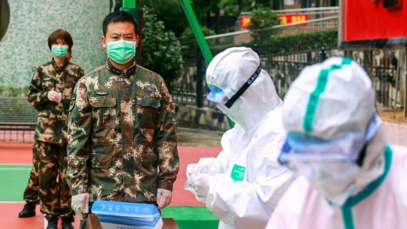 Policías paramilitares chinos esperan ser examinados por el coronavirus COVID-19 cuando regresan de sus vacaciones a Shenzhen en la provincia de Guangdong del sur de China, el 11 de febrero de 2020. (STR/AFP vía Getty Images)