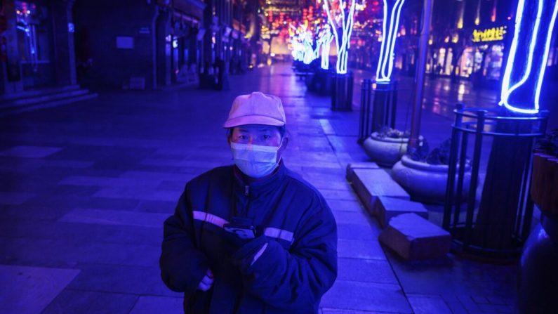 Una trabajadora china en una calle comercial casi vacía y cerrada en Beijing, China, el 12 de febrero de 2020. (Kevin Frayer/Getty Images)