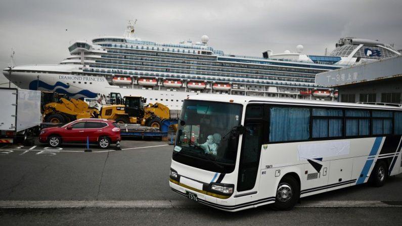 Un autobús con un conductor cubierto de un equipo de protección completo sale del muelle junto al crucero Diamond Princess, que tiene alrededor de 3600 personas en cuarentena a bordo debido a los temores del nuevo coronavirus COVID-19, en la Terminal de Cruceros del Muelle Daikoku en el puerto de Yokohama el 14 de febrero de 2020. (Foto de CHARLY TRIBALLEAU/AFP vía Getty Images)