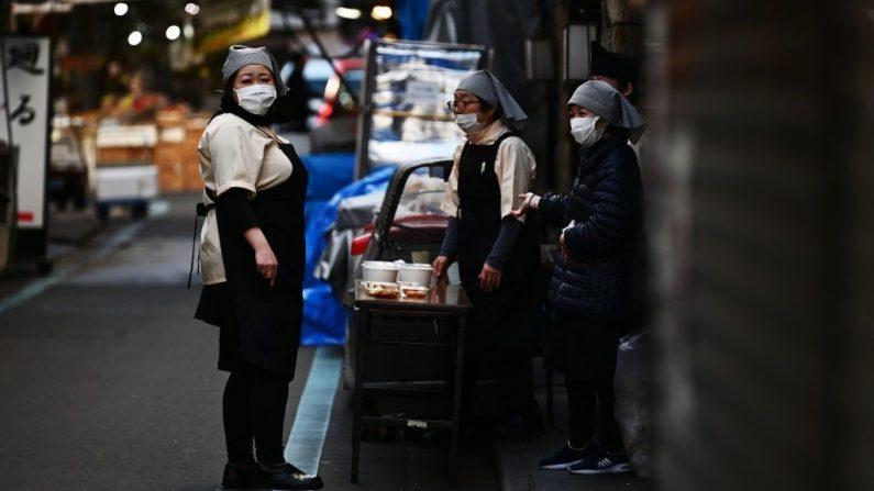 Vendedoras charlan en una calle de la zona de Tsukiji de Tokio el 17 de febrero de 2020. - Japón dijo que el 17 de febrero cancelaría una reunión pública para celebrar el cumpleaños del nuevo emperador Naruhito el 23 de febrero, ya que crece el temor por la propagación del nuevo coronavirus en el país. (Foto de CHARLY TRIBALLEAU/AFP vía Getty Images)