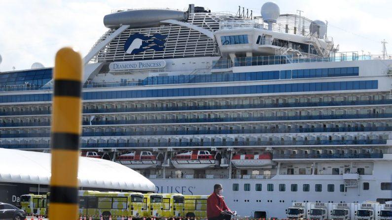 Un hombre pasa por los autobuses urbanos alineados para transportar al primer lote de pasajeros que desembarcan del crucero Diamond Princess en la Terminal de Cruceros Daikoku Pier en Yokohama el 19 de febrero de 2020. (Charly Triballeau/AFP a través de Getty Images)