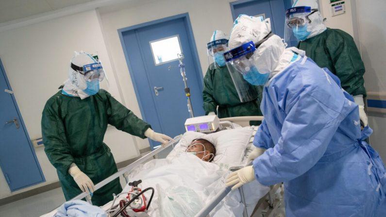 El personal médico transfiere a un paciente infectado por el nuevo coronavirus en un hospital en Wuhan, en la provincia central de Hubei, China, el 22 de febrero de 2020. (STR/AFP a través de Getty Images)