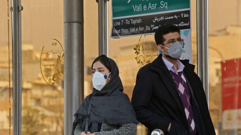 Personas con máscaras protectoras se paran en una estación de autobuses en la capital iraní, Teherán, el 24 de febrero de 2020. - El gobierno iraní fue acusado de encubrir el brote más mortífero del coronavirus COVID-19 fuera de China, ya que desestimó las afirmaciones de que el número de víctimas podría llegar a 50. (ATTA KENARE/AFP vía Getty Images)