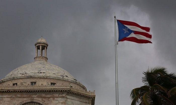 La bandera puertorriqueña ondea cerca del edificio del Capitolio mientras los residentes de la isla se enfrentan a la deuda de 72 mil millones de dólares del gobierno el 1 de julio de 2015 en San Juan, Puerto Rico. (Joe Raedle/Getty Images)