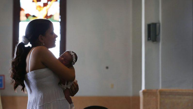 Una madre cubana sostiene a su bebé mientras visita la iglesia El Cobre en Santiago de Cuba, Cuba, el 19 de septiembre de 2015. (Joe Raedle / Getty Images)