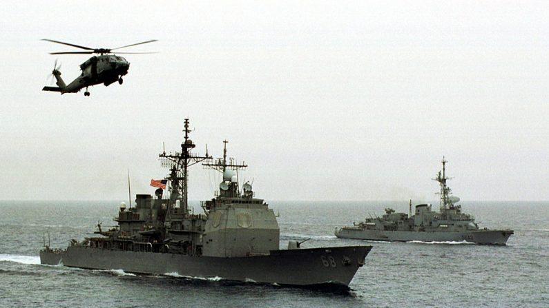 Un Hs-60 Seahawk vuela alrededor del USS Anzio mientras el Mountcalm estadounidense y francés navegan hacia su posición para el ejercicio fotográfico conjunto de la flota estadounidense y francesa el 27 de septiembre de 1998 en el Golfo Pérsico. (U.S. Navy/Getty Images)