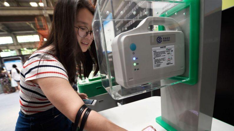 Una mujer prueba una máquina que comprueba los vasos sanguíneos mediante angiografía infrarroja en la exposición del Festival Internacional de la Vida Futura de Hangzhou, en China. La exposición mostró las tecnologías que se están desarrollando para su uso en la mejora de los estilos de vida en el futuro.  (STR/AFP a través de Getty Images)