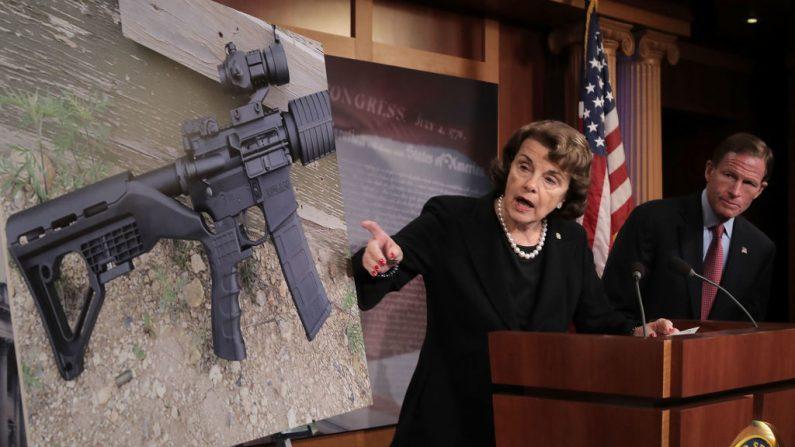 """La senadora Dianne Feinstein (D-Calif.) Y el senador Richard Blumenthal (D-Conn.) Señalan una fotografía de un rifle con un """"stock de golpes"""" durante una conferencia de prensa para anunciar la propuesta de legislación de control de armas en el Capitolio de los Estados Unidos en Washington el 4 de octubre de 2017. (Chip Somodevilla / Getty Images)"""