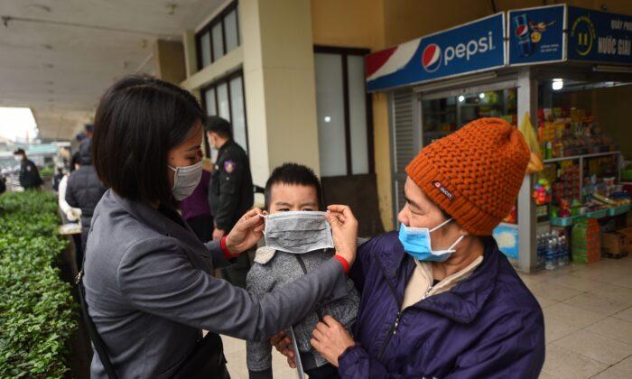 Un empleado (Izq.) le pone una máscara protectora a un niño en una estación de tren en Hanoi, Vietnam, el 2 de febrero de 2020. (NHAC NGUYEN/AFP a través de Getty Images)