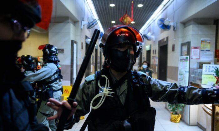 Policía antidisturbios se encuentra a la entrada de un edificio residencial mientras los residentes protestan contra los planes de una urbanización local vacía que se convertirá en un campamento temporal de cuarentena para pacientes y personal médico de primera línea por un brote de virus similar al del SARS que comenzó en la ciudad china de Wuhan, en el distrito Fanling de Hong Kong, el 26 de enero de 2020. (PHILIP FONG/AFP a través de Getty Images)