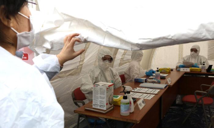 Funcionarios médicos esperan a las personas que quieren hacerse la prueba del nuevo coronavirus en el distrito comercial de Myeongdong en Seúl, Corea del Sur, el 31 de enero de 2020. (Chung Sung-Jun/Getty Images)