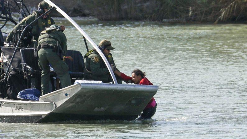 Oficiales en un bote de Aduanas y Protección Fronteriza de Estados Unidos rescatan a una mujer y un niño que se quedaron atrapados intentando cruzar ilegalmente el Río Grande hacia Estados Unidos en Eagle Pass, Texas, el 16 de febrero de 2019. (Charlotte Cuthbertson / The Epoch Times)