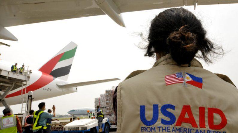 Una trabajadora de USAID observa cómo se descargan los suministros de ayuda en el aeropuerto internacional de Manila el 13 de octubre de 2009. (Jay Directo/AFP vía Getty Images)