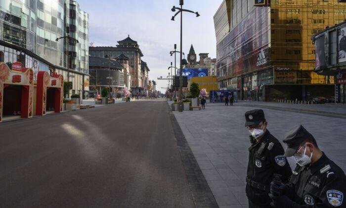 Dos guardias de seguridad chinos vigilan una calle comercial casi vacía en uno de los barrios más concurridos de Wangfujing en Beijing, China, el 18 de febrero de 2020. (Kevin Frayer / Getty Images)
