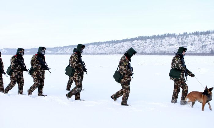Guardias fronterizos de la policía paramilitar china entrenan en la nieve en el condado de Mohe, en la provincia de Heilongjiang, al noreste de China, en la frontera con Rusia, el 12 de diciembre de 2016. Mohe es el punto más septentrional de China, con un clima subártico en el que los guardias fronterizos operan con temperaturas tan bajas como -36°C. (STR/AFP vía Getty Images)