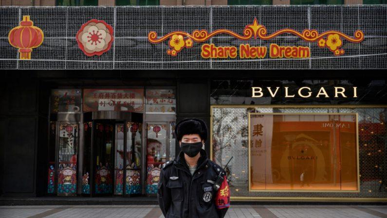 Un guardia de seguridad chino usa una máscara protectora mientras se para en una calle comercial en Beijing, China, el 18 de febrero de 2020. (Kevin Frayer/Getty Images)