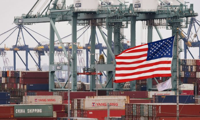 Contenedores de envío internacional junto a una bandera estadounidense en el Puerto de Los Ángeles, en Long Beach, California, el 14 de mayo de 2019. (Mark Ralston/AFP/Getty Images)