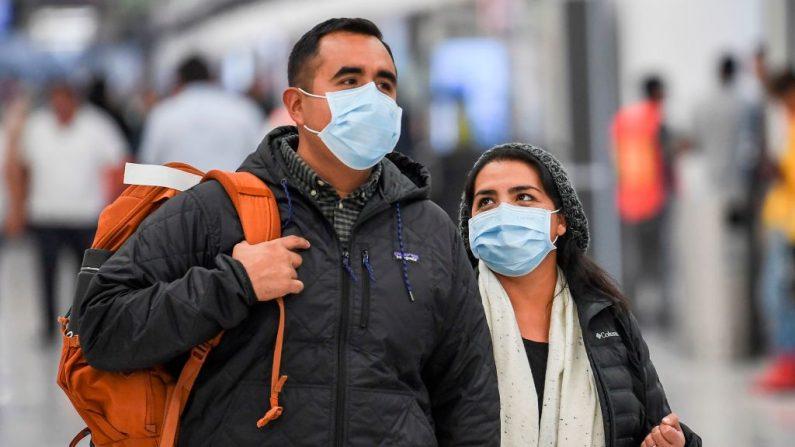 Pasajeros llevan máscaras protectoras contra la propagación del coronavirus cuando llegan al Aeropuerto Internacional de la Ciudad de México, el 29 de enero de 2020. (PEDRO PARDO/AFP vía Getty Images)