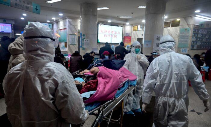 El personal médico con ropa de protección llega con un paciente al Hospital de la Cruz Roja de Wuhan en la ciudad de Wuhan, China, el 25 de enero de 2020. (Hector Retamal/AFP vía Getty Images)