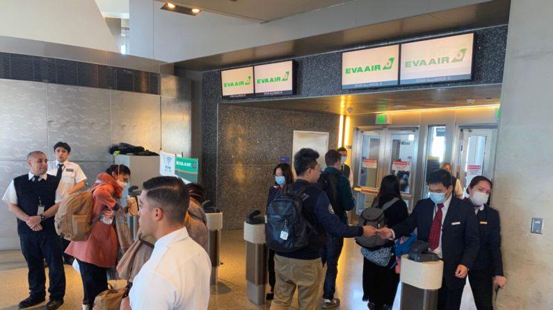 Los empleados de EVA Air son vistos en el Aeropuerto Internacional de Los Ángeles (LAX) usando máscaras, para prevenir la infección por coronavirus, COVID-19 en Los Ángeles, California, el 12 de febrero de 2020. (Daniel Slim/AFP a través de Getty Images)