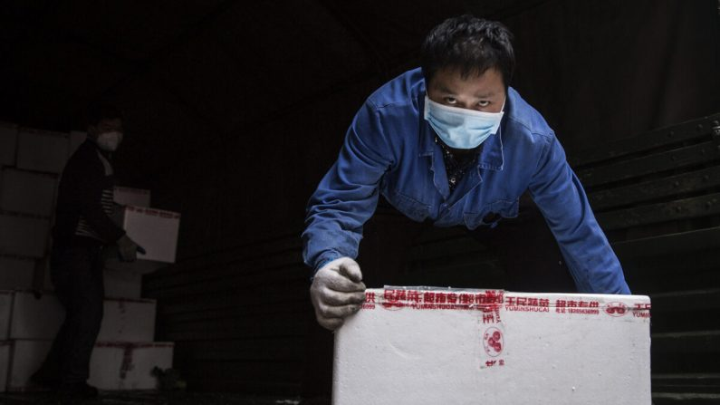 Un empleado usa una máscara protectora mientras transporta verduras desde camiones en un hospital en Wuhan, China, el 10 de febrero de 2020. (Getty Images)