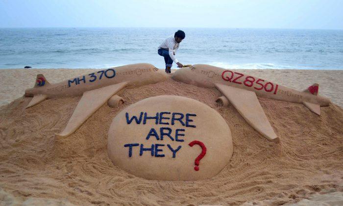 El artista de arena de la India Sudarsan Pattnaik da los últimos toques a su escultura de arena que representa dos aviones desaparecidos, Air Asia QZ8501 y Malayasia Airlines MH370 en la playa del Mar Dorado en Puri, al este de Bhubaneswar en una foto de archivo. (STRDEL/AFP/Getty Images)